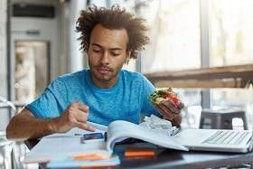 A person eating and studying